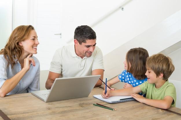 Genitori con computer portatile che aiutano a colorare i bambini