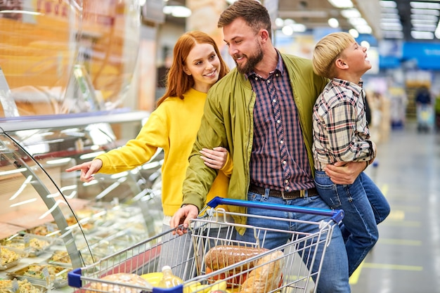 Genitori con figlio irrequieto in drogheria, donna che sceglie cibo per cena mentre suo marito tiene il figlio in mano, vicino a vetrine con cibo