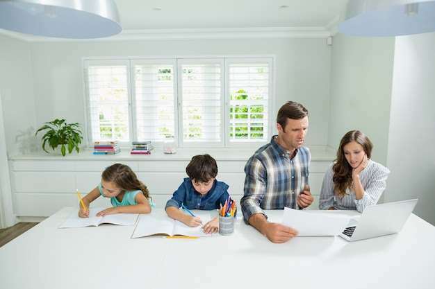Genitori che lavorano con il computer portatile e bambini che studiano nel salone