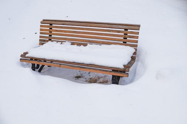 Panchina nel parco coperto da neve pesante. panca in legno solitario sotto la caduta di neve. giorno di nevicate. perfetto per le vacanze di natale