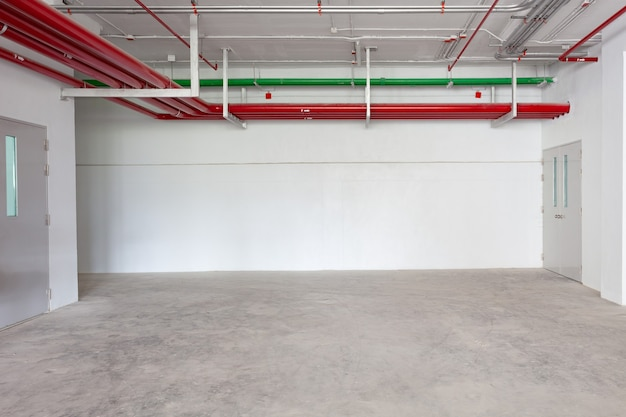 Parcheggio garage interno edificio industriale idrante con tubi dell'acqua in edificio industriale spazio vuoto per sfondo industria.