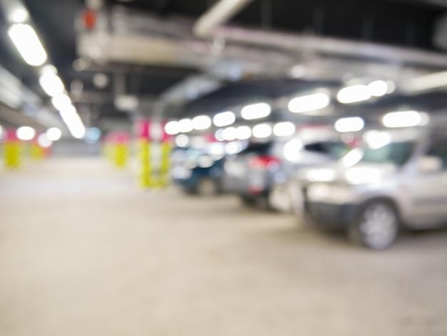 Garage sotterraneo con auto, interni industriali. luce al neon in un luminoso edificio industriale.