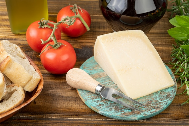 Parmigiano, pomodori, olio d'oliva, vino, pane ed erbe aromatiche sul tavolo di legno. cucina mediterranea.