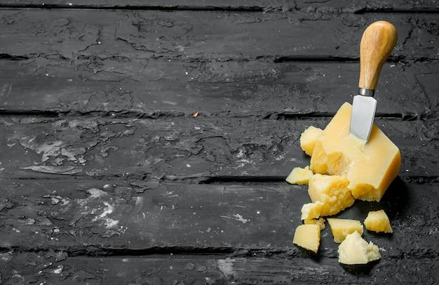 Parmigiano reggiano con coltello nero sul tavolo rustico.
