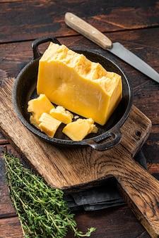 Pezzo di formaggio duro di parmigiano in una padella. fondo di legno scuro. vista dall'alto.