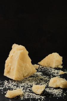Parmigiano a pezzi su un vecchio tavolo da cucina, formaggio stagionato di fattoria. prodotto naturale della cucina mediterranea