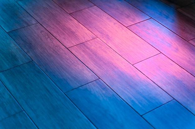 Pista da ballo in parquet rinfrescata da luci colorate. luci da discoteca sul pavimento