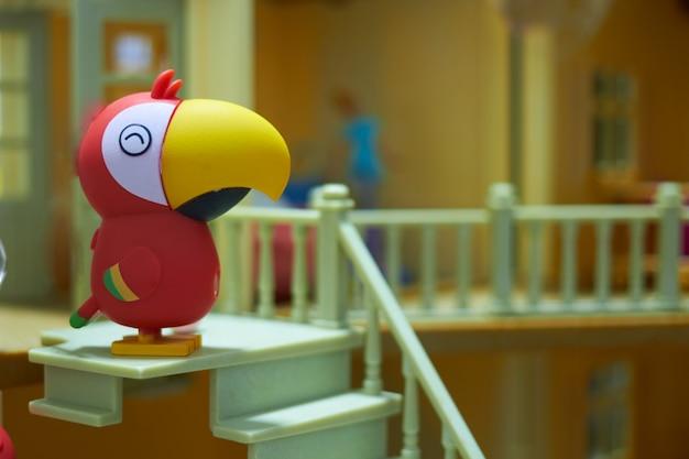 La bambola pappagallo si erge sul resto delle scale della casa delle bambole Foto Premium