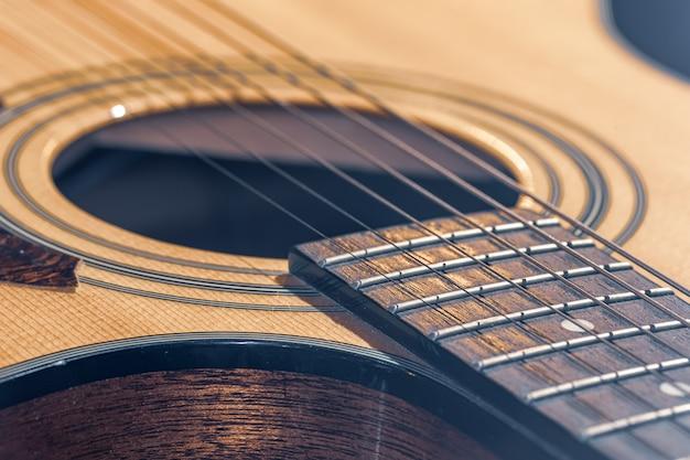 Parte di una chitarra acustica, tastiera per chitarra con corde su sfondo nero con riflessi.