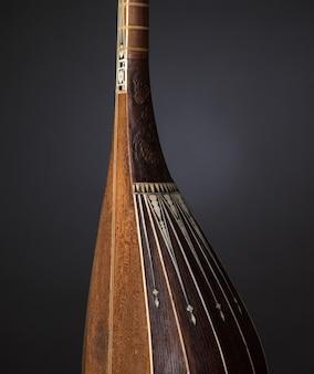 Parte antico strumento musicale a corde asiatico su sfondo nero con retroilluminazione