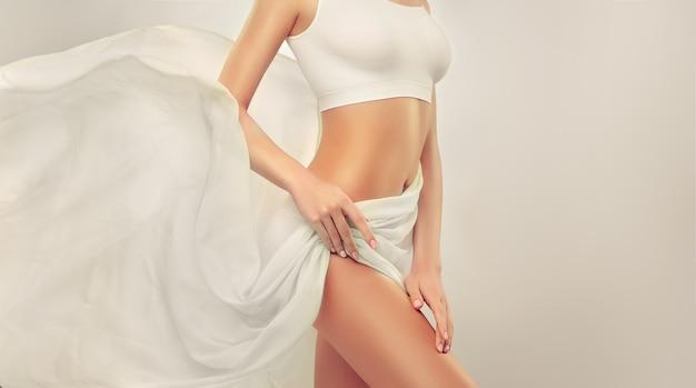 Parte del corpo di donna attraente, fianchi e pancia snella tonica, coperta da tenera