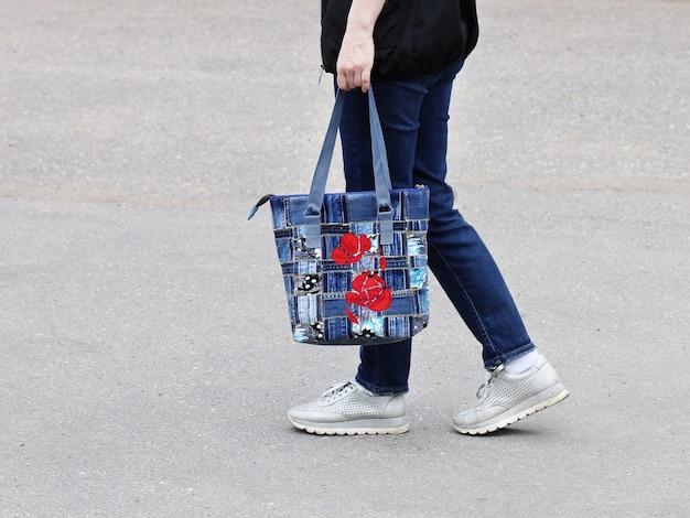 Parte del corpo di donna in jeans e scarpe da ginnastica che porta borsa cucita da denim