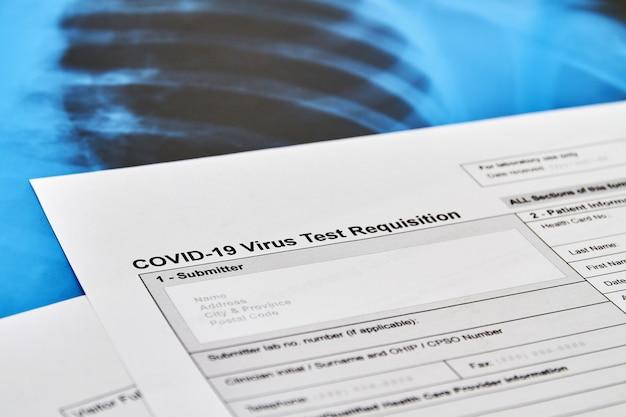 Parte del test del virus covid-19 modulo di richiesta sullo sfondo della radiografia polmonare. concetto di protezione dal coronavirus. avvicinamento