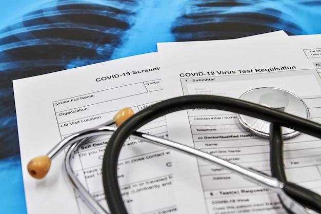Parte del test del virus covid-19 modulo di richiesta e stetoscopio sullo sfondo della radiografia polmonare. concetto di protezione dal coronavirus. avvicinamento