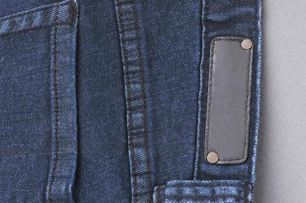 Parte di pantaloni in denim con tasche posteriori ed etichetta, primo piano