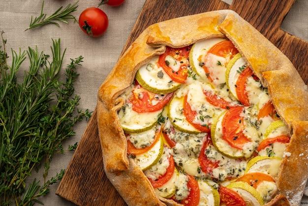 Parte di galette salata fatta in casa con verdure, torta integrale con pomodori, zucchine, gorgonzola gorgonzola. crostata rustica in crosta su tovaglia tessile di lino scuro.