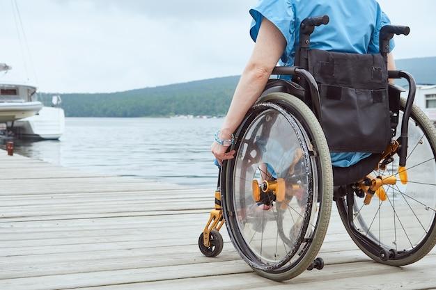 Parte dell'immagine di una donna su una sedia a rotelle in piedi su un molo di legno