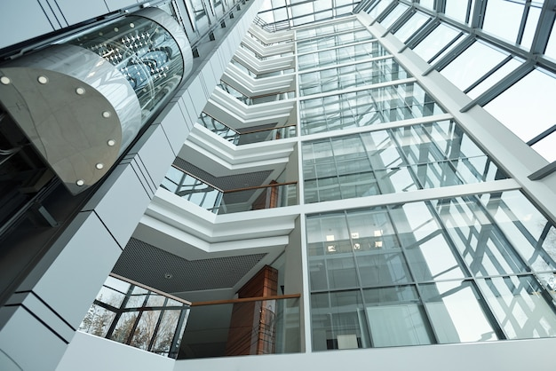Parte degli interni del centro ufficio contemporaneo con persone in ascensore che si muovono verso l'alto, balconi, pareti e finestre