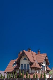 Parte di una moderna casa di mattoni sotto un tetto di tegole su un cielo. cottage con balcone. casa di legno. vivere nella natura. pietra naturale di finitura