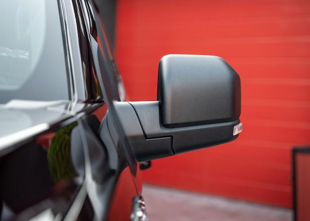 Parte della nuova auto suv nera. specchietto retrovisore in primo piano. particolare esterno.