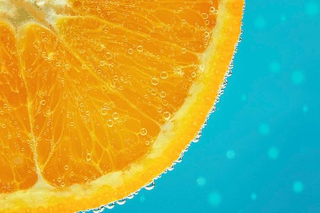 Parte dell'arancia con una bolla sullo sfondo blu. primo piano.