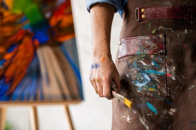 Parte del pittore professionista in grembiule sporco che tiene il pennello in mano