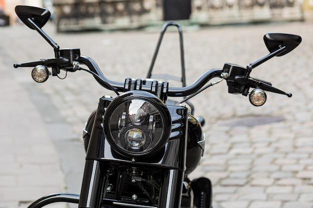 Parte di una moto retrò nera con un grande faro
