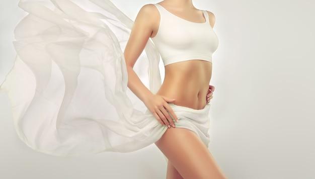 Parte dei fianchi del corpo della donna e del ventre tonico snello ricoperto da un tessuto di seta tenera