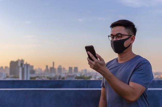 Messa a fuoco parziale dell'uomo asiatico che indossa la maschera per il viso per proteggersi dai virus e fare una videochiamata con lo smartphone.