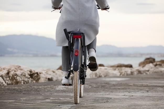 Vista parziale della bicicletta con donna, vestiti grigi, spiaggia sullo sfondo. (focus sulla ruota della bicicletta)