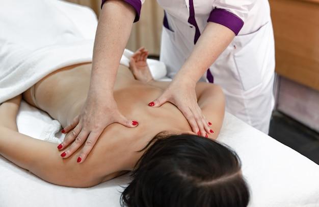 Vista parziale del massaggiatore che massaggia la schiena della giovane donna sdraiata sul lettino da massaggio.
