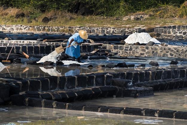 Una vista parziale di una donna che mette il sale in polvere su una superficie bianca.la produzione di sale isola di mauritius