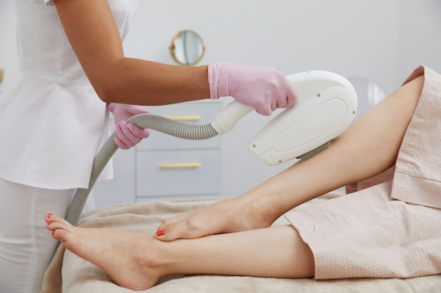 Vista parziale della donna che riceve l'epilazione con la depilazione laser sulla gamba in un salone