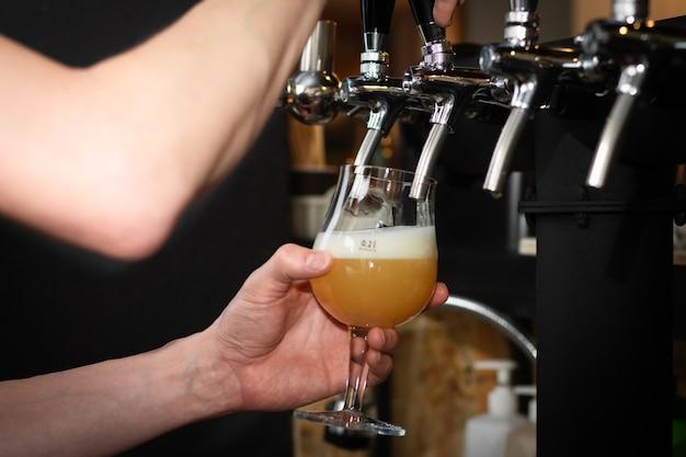Mano parzialmente sfocata, versando birra dal rubinetto argenteo in un pub