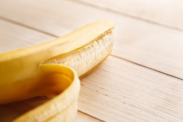 Banana gialla matura parzialmente sbucciata sulla tavola di legno