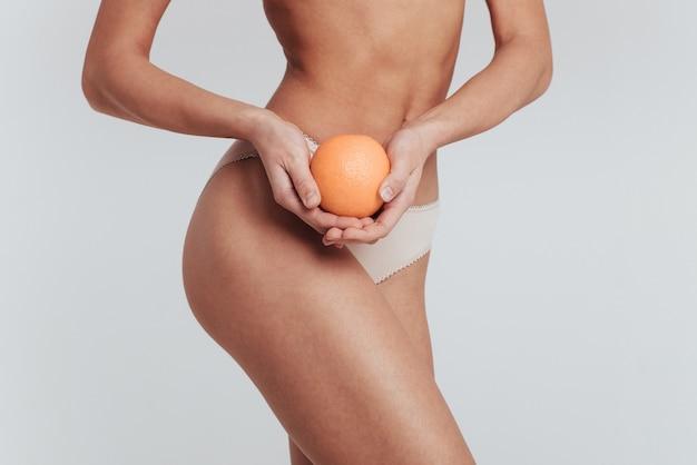Foto di particelle di ragazza in biancheria intima bianca in piedi al muro bianco e tenendo l'arancia.