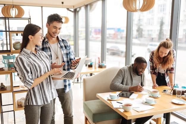 Decisione del partner. la giovane donna graziosa sta tenendo il laptop e sta vicino al suo collega maschio durante la discussione delle informazioni importanti di affari.