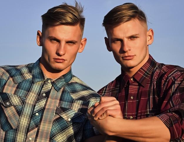Partnership, futuro, supporto e fiducia. fratelli gemelli uomo all'aperto, relazioni. ragazzi caucasici in magliette con facce serie. futuro e libertà, sostegno e fiducia. l'amicizia dell'uomo