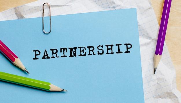Testo di partenariato scritto su una carta con le matite in ufficio