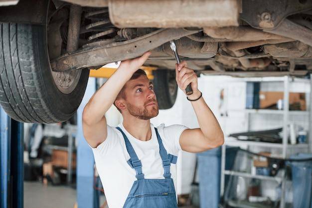 Parti dell'auto. l'impiegato con l'uniforme di colore blu lavora nel salone dell'automobile