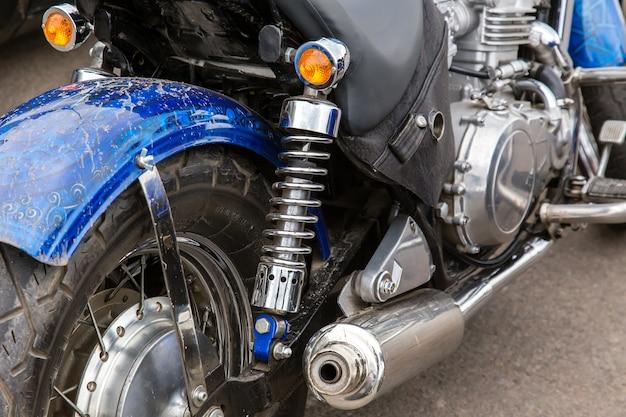 Parti di una moto da corsa. primo piano della ruota, dell'ammortizzatore e del tubo di scarico.