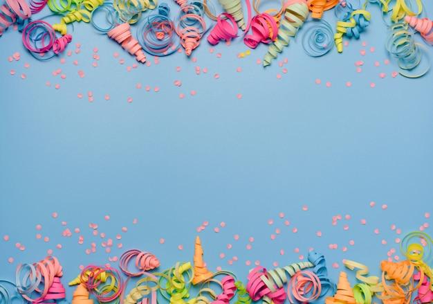 Sfondo festa con stelle filanti colorate per festeggiare il compleanno. spazio con coriandoli sparsi.
