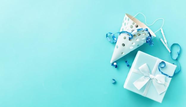 Sfondo festa con stelle filanti, confezione regalo, candele e cappelli di compleanno sull'azzurro