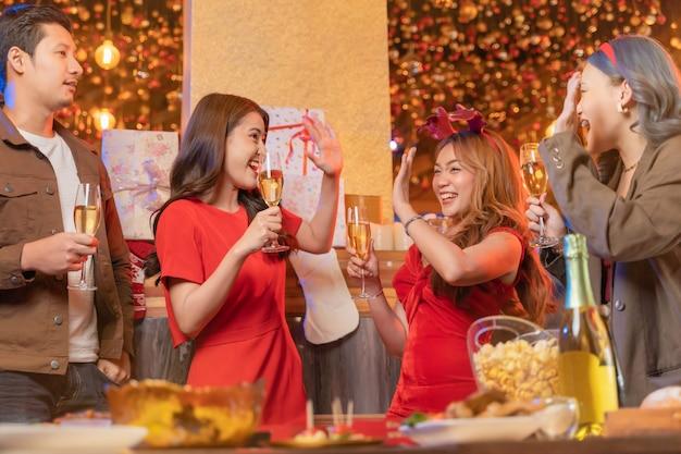 Festa di belle amiche asiatiche femmine e maschi che celebrano la felicità degli amici la vigilia di natale