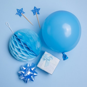 Sfondo festa o compleanno. palloncino, confezione regalo su sfondo blu vista dall'alto. stile piatto.