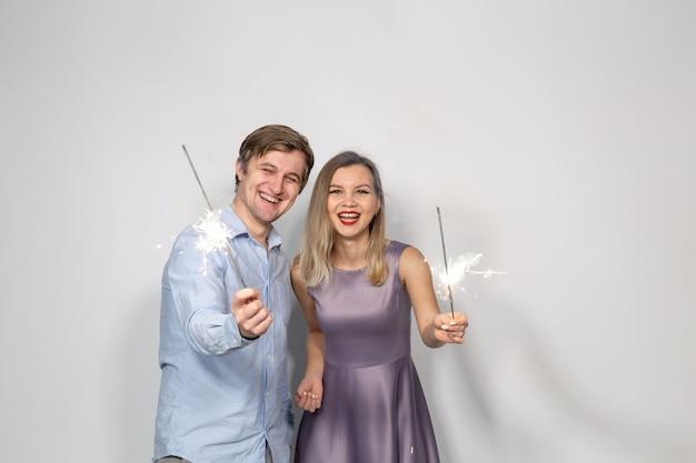 Festa, celebrazione, capodanno, evento e concetto di vacanze - uomo vestito con camicia blu e donna vestita con abito viola tenere un bastone di fuochi d'artificio