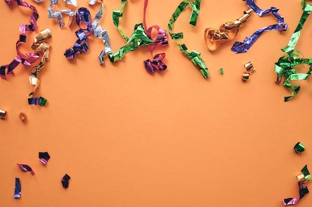 Partito coriandoli colorati su sfondo carta pastello. scintille, glitter, cornice orpello. appartamento laico, vista dall'alto, copia spazio banner.