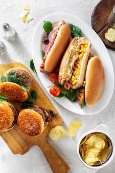 Partito tavolo da pranzo con diversi hot dog fatti in casa e hamburger vista dall'alto