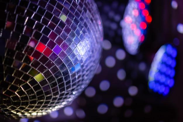 Sfera dello specchio della discoteca del partito che riflette le luci viola.