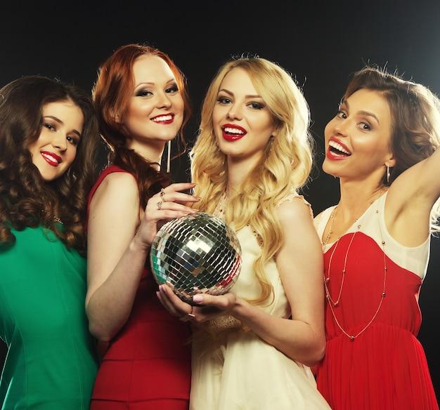 Ragazze festaiole con palla da discoteca, felici e sorridenti.